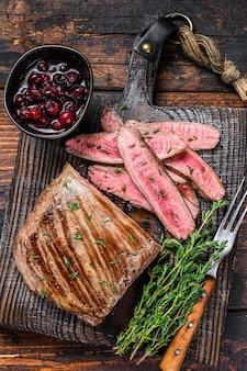 Bistecca di carne di manzo affettato barbecue su un tagliere di legno