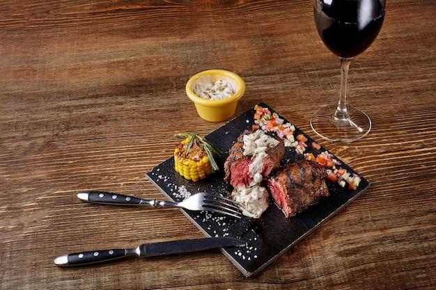 Bistecca alla griglia con un bicchiere di vino rosso come primo piano su tavola nera su fondo di legno