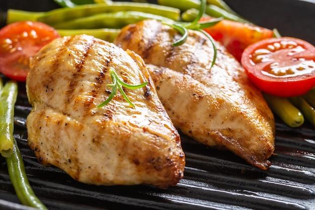 Petti di pollo alla brace su una griglia con verdure verdi fresche e pomodorini e rametti di rosmarino.