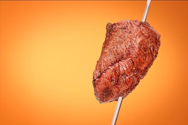 Barbecue picanha alla brace con sfondo arancione chiamato anche churrasco