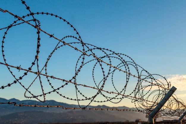 Recinto del filo spinato contro il cielo blu e le montagne. restrizioni, proprietà privata