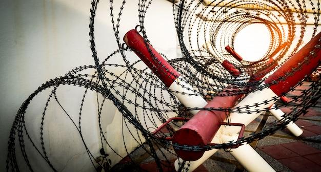 Recinto di filo spinato. muro di prigione o prigione. sistema di sicurezza. zona privata o zona militare di pericolo. cancello o ingresso proibito. area proibita. colore rosso e bianco su palo.