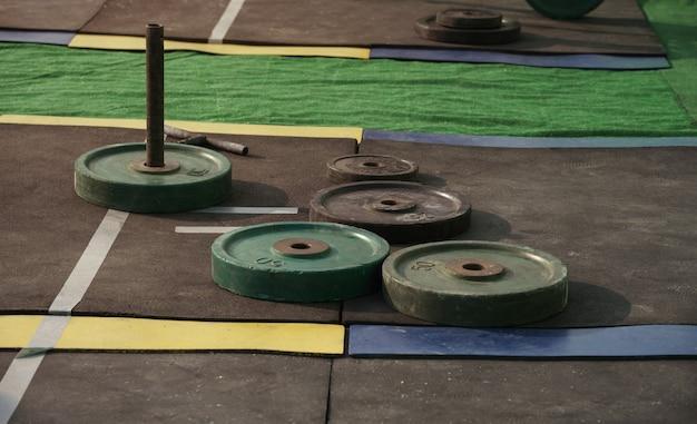 Dischi del peso del bilanciere sul pavimento di gomma dello stadio con lo spazio della copia