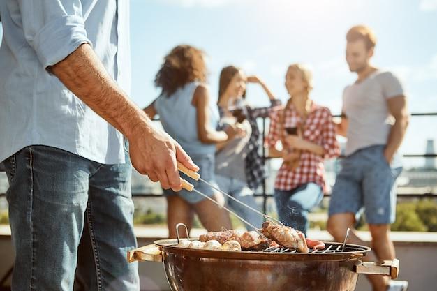 Uomo del tempo del barbecue che griglia la carne alla griglia mentre si trova sul tetto con gli amici