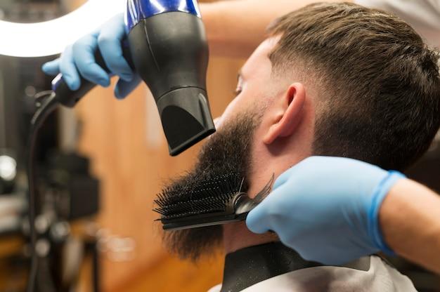 Barbiere che asciuga la barba del cliente maschio