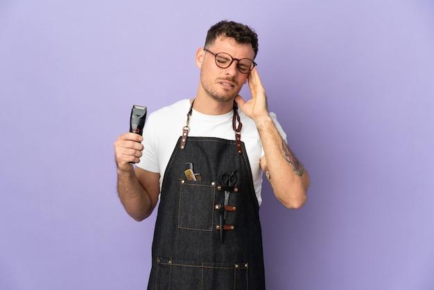 Uomo caucasico del barbiere in un grembiule isolato sulla parete viola con mal di testa