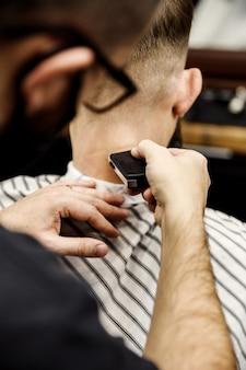 Il barbiere taglia un cliente in un elegante barbiere. taglio di capelli maschile con un rasoio