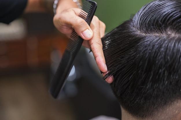 Barbiere taglio di capelli tagliare i capelli del cliente con le forbici e il pettine nel negozio di barbiere
