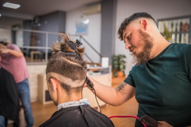 Barbiere che taglia i capelli del suo cliente in un barbiere