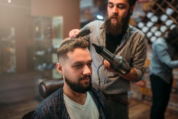 Barbiere asciugare i capelli del cliente con l'asciugacapelli.