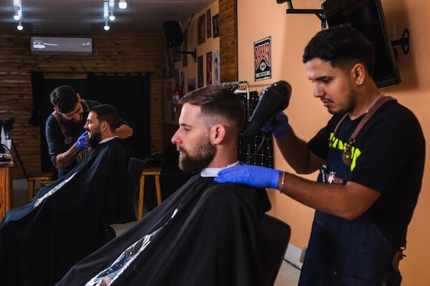 Barbiere che asciuga i capelli del suo cliente con un asciugacapelli