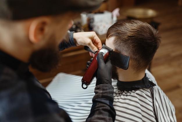 Il barbiere con il cappello taglia i capelli del cliente. il barbiere professionale è un'occupazione alla moda. parrucchiere maschio e cliente nel salone di capelli in stile retrò