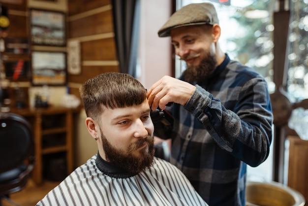 Il barbiere con il cappello taglia i capelli del cliente. il barbiere professionale è un'occupazione alla moda. parrucchiere maschio e cliente nel salone di capelli in stile retrò Foto Premium