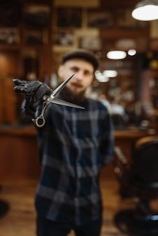 Il barbiere in cappello e guanti mostra sciccors. il barbiere professionale è un'occupazione alla moda. parrucchiere uomo nel salone di parrucchiere in stile retrò