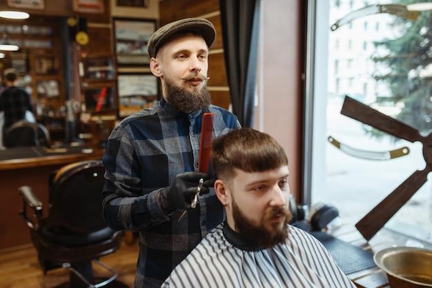 Il barbiere tiene il pettine e taglia i capelli del cliente. il barbiere professionale è un'occupazione alla moda. parrucchiere maschio e cliente nel salone di capelli in stile retrò