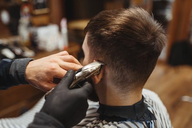 Il barbiere tiene il pettine e taglia i capelli del cliente. il barbiere professionale è un'occupazione alla moda. parrucchiere uomo e cliente nel salone in stile retrò