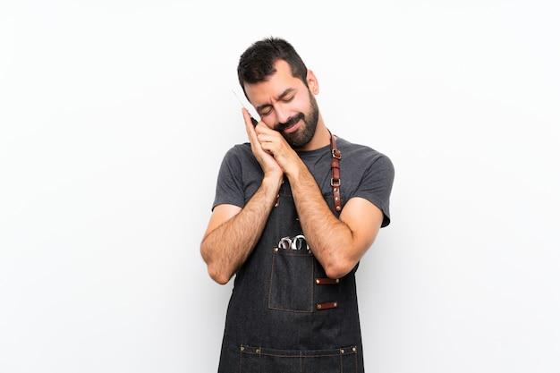 Uomo del barbiere in un grembiule che fa gesto di sonno nell'espressione dorable