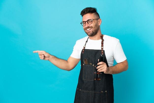 Uomo del barbiere in un grembiule che punta il dito di lato e presenta un prodotto