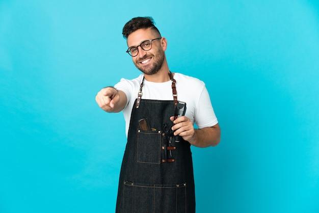 Uomo del barbiere in un grembiule che punta davanti con felice espressione