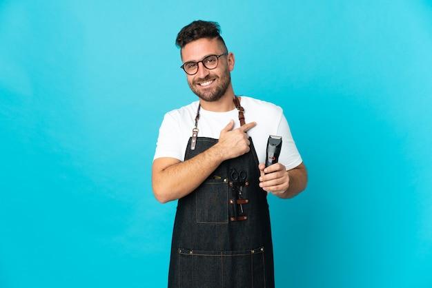 Uomo del barbiere in un grembiule che punta al lato per presentare un prodotto
