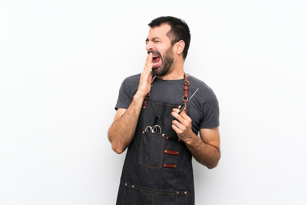 Uomo del barbiere in un grembiule che sbadiglia e che copre la bocca spalancata con la mano
