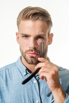L'uomo del barbiere con la barba ed i baffi tiene il parrucchiere del rasoio diritto che dimostra del negozio di barbiere