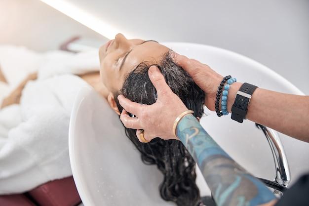 Barbiere che massaggia la testa del cliente