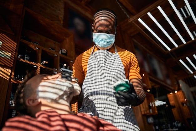 Barbiere in maschera medica che applica crema da barba sul viso del cliente