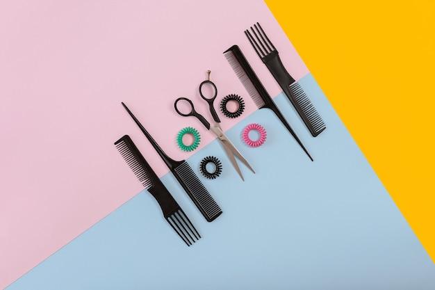 Set da barbiere con pettini e forbici sullo sfondo di carta di colore rosa, giallo, blu. vista dall'alto. copia spazio. natura morta. modello. lay piatto