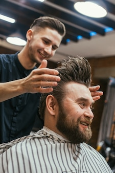 Negozio di barbiere, parrucchiere uomo con barba tagliata. capelli belli e cura, parrucchiere per uomini. taglio di capelli professionale, acconciatura retrò e styling