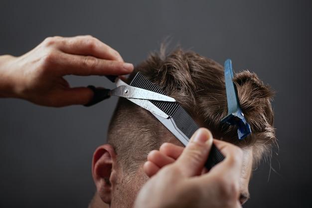 Taglio di capelli maschile da barbiere, acconciatura alla moda.