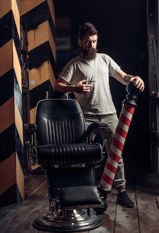 Strumenti del negozio di barbiere sulla vecchia parete di legno con lo spazio della copia. uomo barbuto.