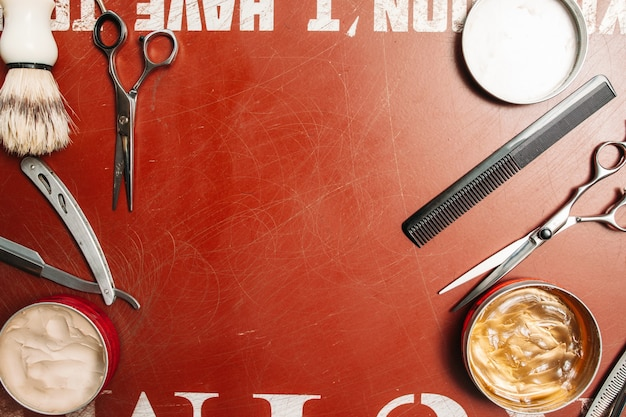Cornice di strumenti del barbiere sulla superficie rossa