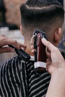 Barbiere utilizzando tagliacapelli e pettine per tagliare i capelli nel negozio di barbiere.