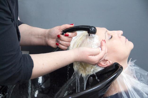 Il barbiere lava i capelli dei clienti un parrucchiere lava i capelli delle donne nel salone