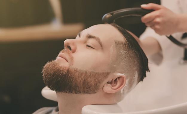 Barbiere che lava la testa dell'uomo barbuto nel negozio di barbiere