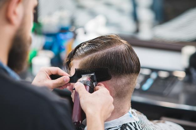 Il barbiere con la barba taglia il giovane con la tosatrice nel salone di bellezza degli uomini.