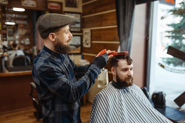 Barbiere con pettine e tagliacapelli elettrico fa un taglio di capelli a un cliente. il barbiere professionale è un'occupazione alla moda. parrucchiere maschio e cliente nel salone di capelli in stile retrò