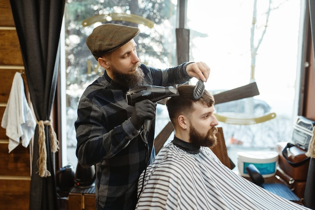 Il barbiere con pettine e asciugacapelli fa un'acconciatura a un cliente. il barbiere professionale è un'occupazione alla moda
