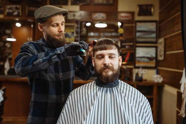 Il barbiere con pettine e forbici fa un taglio di capelli a un cliente. il barbiere professionale è un'occupazione alla moda. parrucchiere maschio e cliente nel salone di capelli in stile retrò