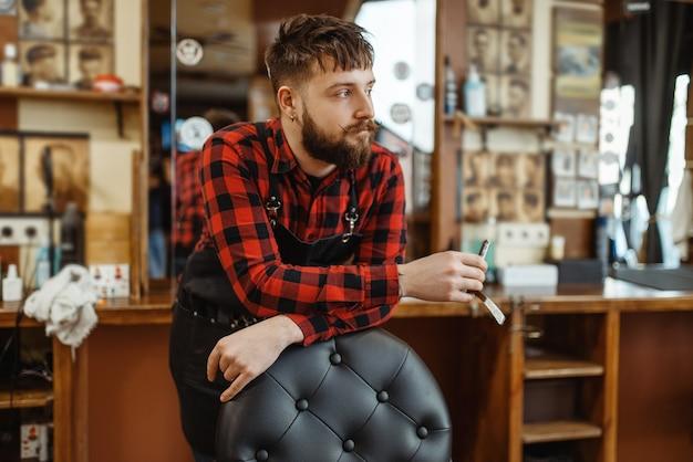 Il barbiere con la lama di rasoio posa alla sedia. il barbiere professionale è un'occupazione alla moda. parrucchiere uomo in stile retrò parrucchiere, accessori per il taglio