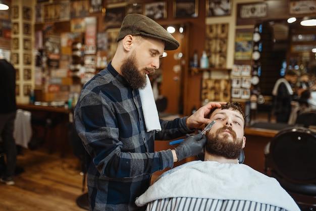 Barbiere con il rasoio, taglio della barba della vecchia scuola. il barbiere professionale è un'occupazione alla moda. parrucchiere maschio e cliente nel salone di parrucchiere