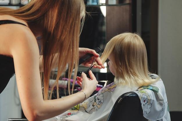 La donna del barbiere fa l'acconciatura graziosa alla moda per la bambina bionda carina nel moderno negozio di barbiere, parrucchiere. il parrucchiere fa la pettinatura per il bambino piccolo nel negozio di barbiere. concept acconciatura e bellezza