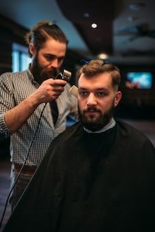 Barbiere che lavora da clipper con l'acconciatura del cliente