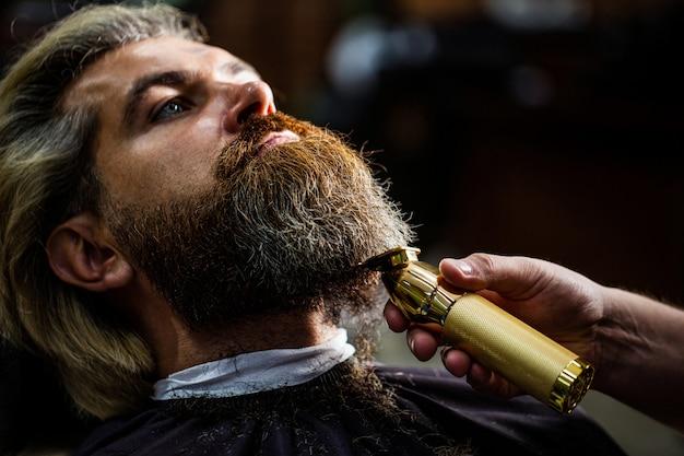 Il barbiere lavora con un regolabarba. cliente di hipster che ottiene taglio di capelli. mani di un parrucchiere con un tagliatore di barba, primo piano.