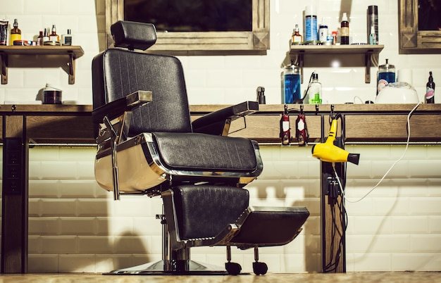 Poltrona da barbiere, parrucchiere moderno e parrucchiere, barbiere per uomo. elegante poltrona da barbiere vintage. sedia da barbiere. tema da barbiere. parrucchiere professionista nell'interno del negozio di barbiere.