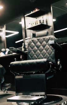Sedia da barbiere. foto ravvicinata di una sedia da barbiere in pelle vegana sintetica in piedi vicino a un posto di lavoro in un barbiere.
