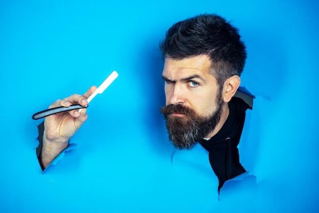 Concetto di barbuto uomo barbuto guarda attraverso la carta un uomo barbuto serio tiene un negozio di barbiere rasoio per