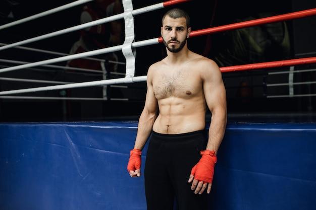 Il pugile a torso nudo si trova vicino al ring. foto di alta qualità