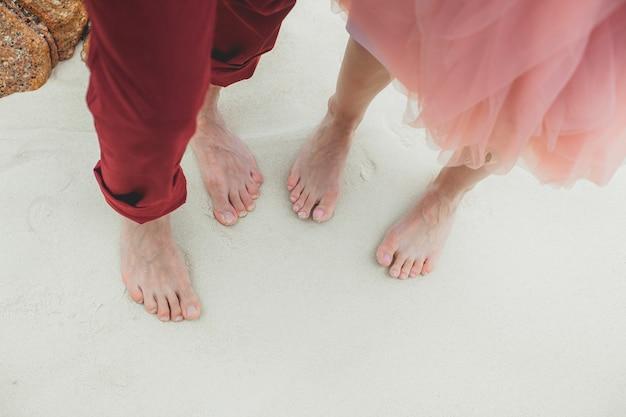 Piedi nudi di un uomo e una donna close-up sulla sabbia.